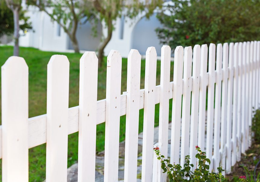County style wooden fence. White fence and green grass